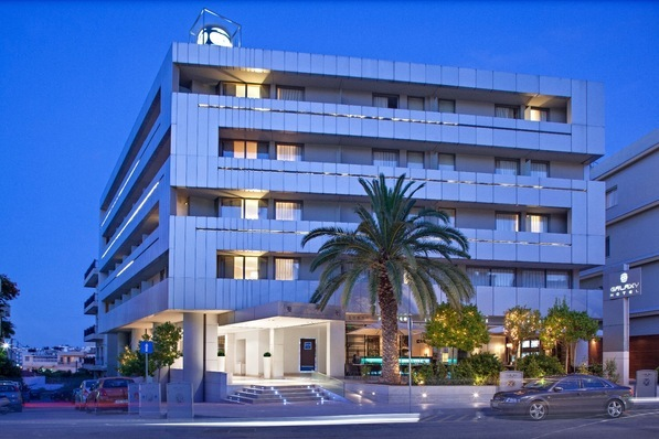 Corner of Galaxy Hotel Iraklio at dusk showing the parking area of our hotel with parking in Heraklion city